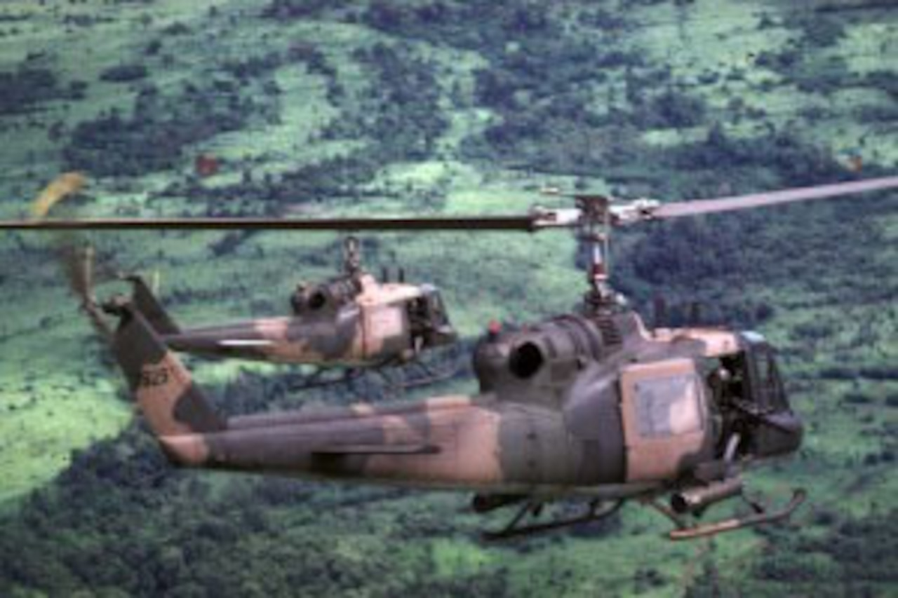 Helicopters fly over a jungle.
