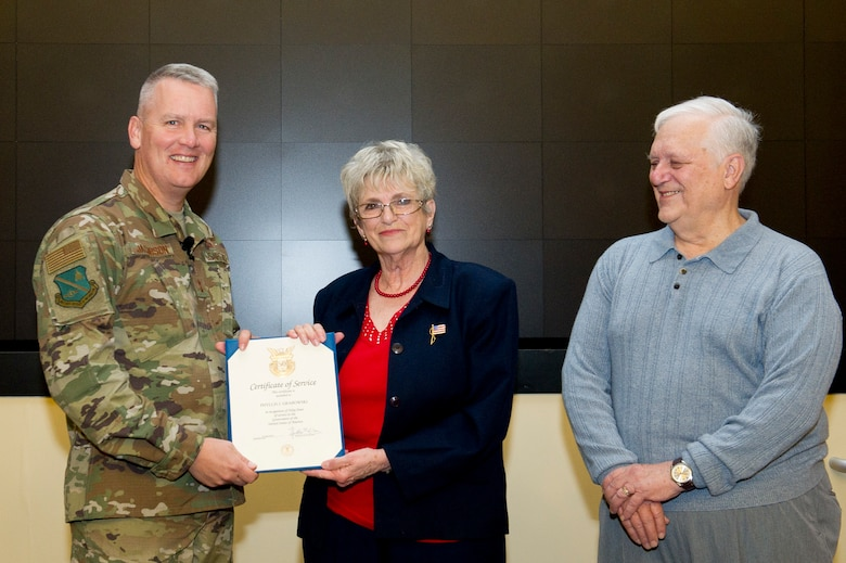 Maj. Gen. James A. Jacobson, Air Force District of Washington commander, left, presents Phyllis Grabowski, AFDW command surgeon's administrative assistant, with a 50-Year Service Certificate of Appreciation as her husband, Chester Grabowski, watches during commander's call at Joint Base Andrews, Md., Nov. 20, 2018. (U.S. Air Force photo by Master Sgt. Michael B. Keller)