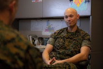 Chaplain sitting in office talking to a Marine