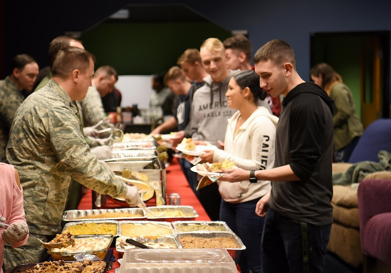 Enlisted Airmen prepare to eat a home-cooked meal Nov. 14, 2018, in the Montgomery Village on Columbus Air Force Base, Mississippi. Base private organizations banded together with Team BLAZE leadership to donate, prepare and serve an early Thanksgiving meal to Airmen who may not get to return home for the holidays. (U.S. Air Force photo by Airman 1st Class Keith Holcomb)