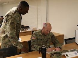 FORT KNOX, Ky. - Lt. Col. Barry Murray, deputy chief of the Strategic Operations and Plans (SOaP) for the 1st Theater Sustainment Command (TSC) Blue Team, assists Maj. John Krigbaum, network assurance officer-in-charge during an SOaP team academic quiz. Forty Soldiers spent a week in the classroom learning the mission of the SOaP team before deploying to Kuwait. (U.S. Army photo by Mr. Brent Thacker)