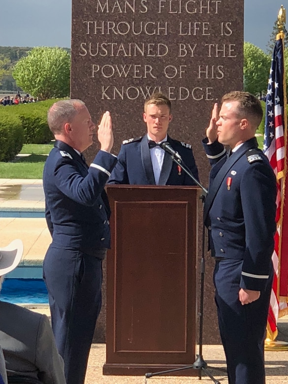 Two men raise hands in an Air Force commissioning ceremony