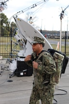 Navy Petty Officer 1st Class Albert A. Givens carries a complete communication Mobile User Objective Service (MUOS), SATCOM system at Joint Task Force Civil Support (JTF-CS) on Nov. 19, 2018. The MUOS system is a critical communication for any crises response. The light compact ability of the system can be used in a field or in transit operations. The MUOS system is ready for deployable conditions anywhere in the world. When directed, JTF-CS is ready to respond in 24 hours to provide command and control of 5,200 federal military forces located at more than 36 locations throughout the nation in support of civil authority response operations to save lives, prevent further injury and provide critical support to enable community recovery. (Official DoD photo by U.S Air Force Tech. Sgt. Michael Campbell/ Released)