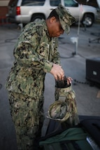 Navy Petty Officer 1st Class Albert A. Givens unpacks a satellite, part of the Mobile User Objective Service (MUOS), SATCOM system at Joint Task Force Civil Support (JTF-CS) on Nov. 19, 2018. The compact satellite enables signal communication in any crisis response. When directed, JTF-CS is ready to respond in 24 hours to provide command and control of 5,200 federal military forces located at more than 36 locations throughout the nation in support of civil authority response operations to save lives, prevent further injury and provide critical support to enable community recovery. (Official DoD photo by U.S Air Force Tech. Sgt. Michael Campbell/ Released)