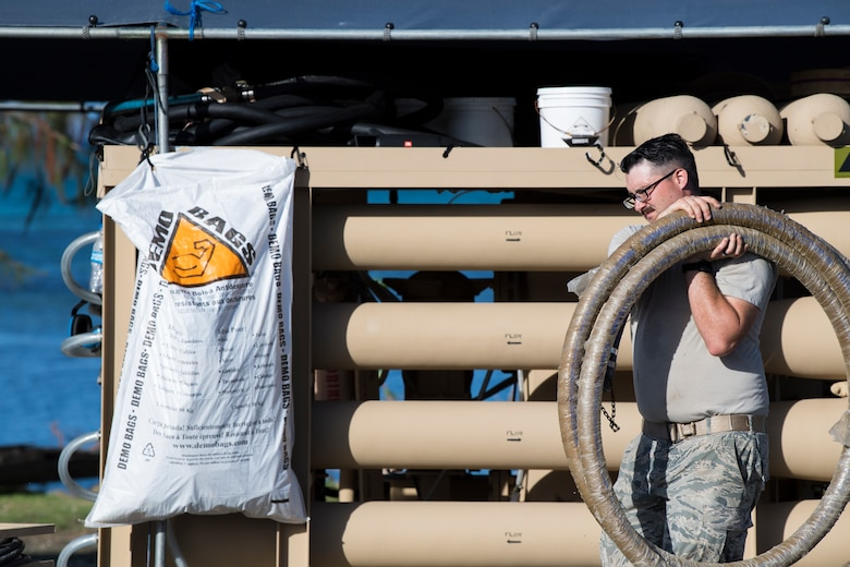 Senior Airman John McGovney, 36th Civil Engineer Squadron water and fuel systems maintainer assigned to Andersen Air Base, Guam, carries a hose during reverse osmosis water purification unit tear down on Saipan, Commonwealth of the Northern Mariana Islands, Nov. 21, 2018, as part of the Super Typhoon Yutu relief effort.