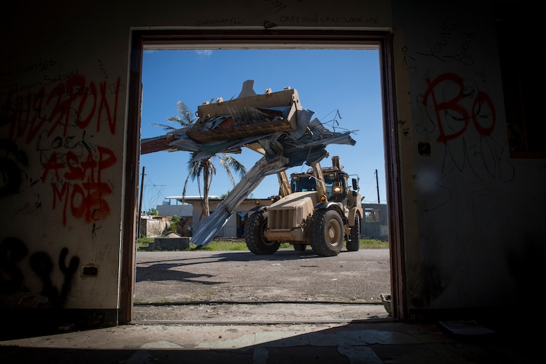 Pvt. Joseph Mafnas, 1224th Engineer Support Company, uses a high mobility evacuation equipment vehicle to remove debris from a street in the village of Chalan Kanoa, Saipan, Commonwealth of the Northern Mariana Islands, Nov. 20, 2018.