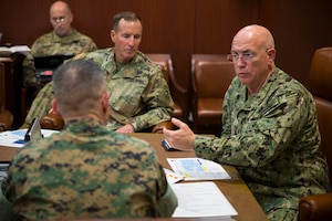 A seated Navy admiral gestures while speaking to a Marine officer.