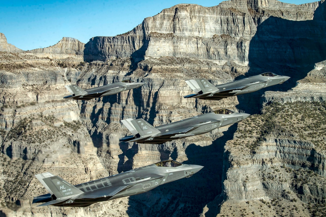 Four Air Force aircraft maneuver near cliffs and mountains.