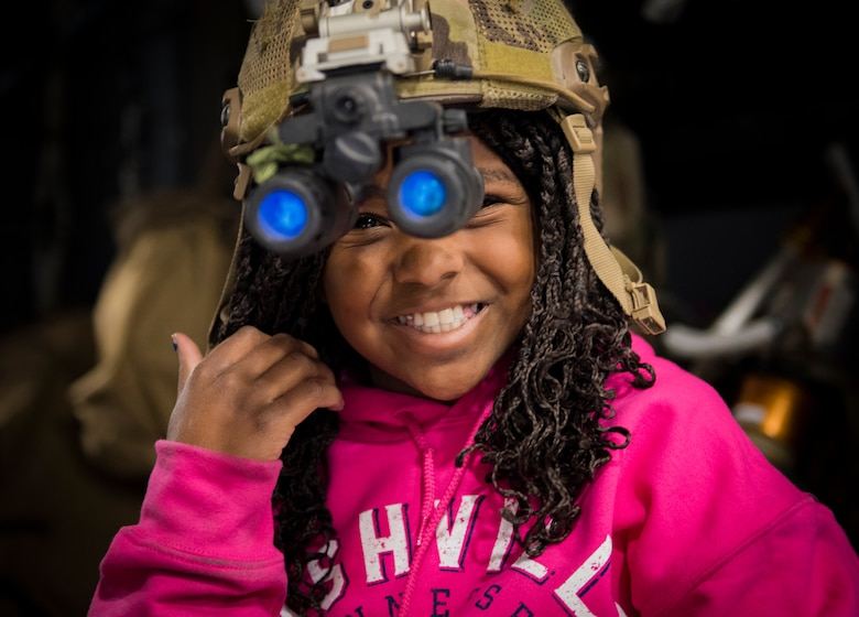 Ruth Cottam tries on a helmet from the 66th Rescue Squadron at Nellis Air Force Base, Nevada, Nov. 16, 2018. Ruth's dad, Dr. Daniel Cottam, was rescued by the 66th RQS when he suffered multiple broken bones from a hiking accident near Zion Canyon, Utah. (U.S. Air Force photo by Airman 1st Class Andrew D. Sarver)