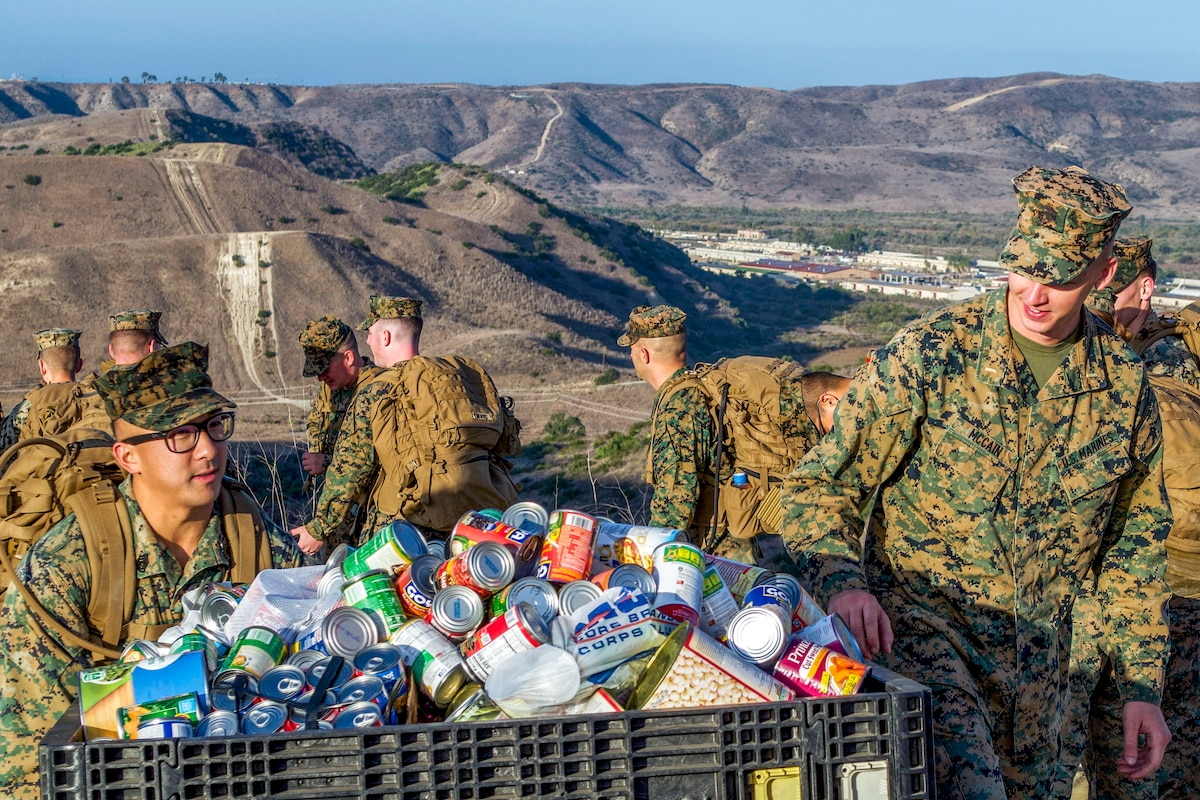 Marines carry a large container of canned food outside.