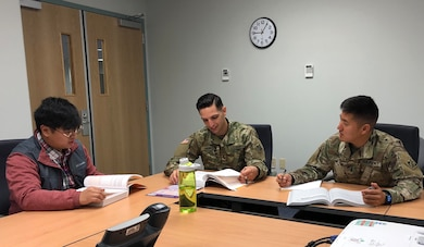 (Left to right) Myles Emsele, 1LT Zachary Hawkins, and 1LT Joshua Jang discuss Project Integration Management tools and techniques at the PMP study group on Nov. 20, 2018 to prepare for the PMP exam.