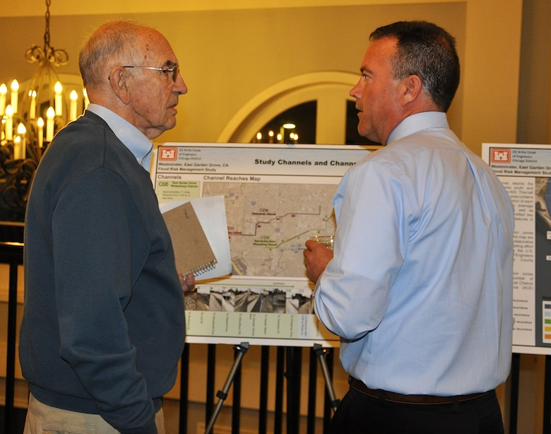 Joel Schmidt, hydraulic engineer with the U.S. Army Corps of Engineers Chicago District, right, speaks to a community member during a Nov. 8 public meeting about the Westminster/East Garden Grove Flood Risk Management Study in Huntington Beach, California.