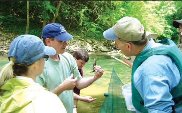 Dr. Richie Kessler, The Nature Conservancy, shows a bottlebrush crayfish to Lisa Morales, Corps headquarters, and John Paul Woodley, Jr., Assistant Secretary of the Army for Civil Works, during a visit to Green River.