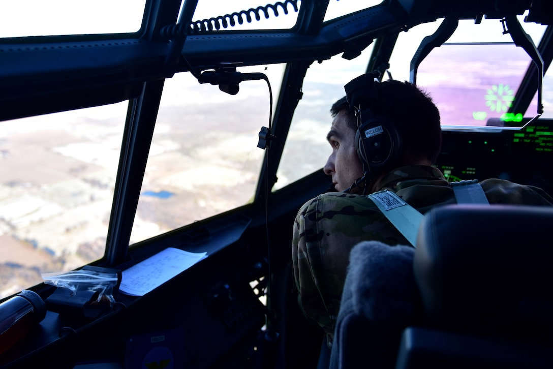 A man wearing a flight suite with a headset on looks out the window of a C-130J while in flight.