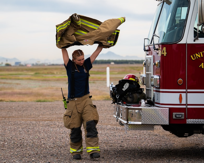Staff Sgt. Ashley Eisenbarth, 56th Civil Engineer Squadron Fire Department fire captain, dons her gear before starting a joint aircraft and structural live fire training, Nov. 14, 2018, at Luke Air Force Base, Ariz.
