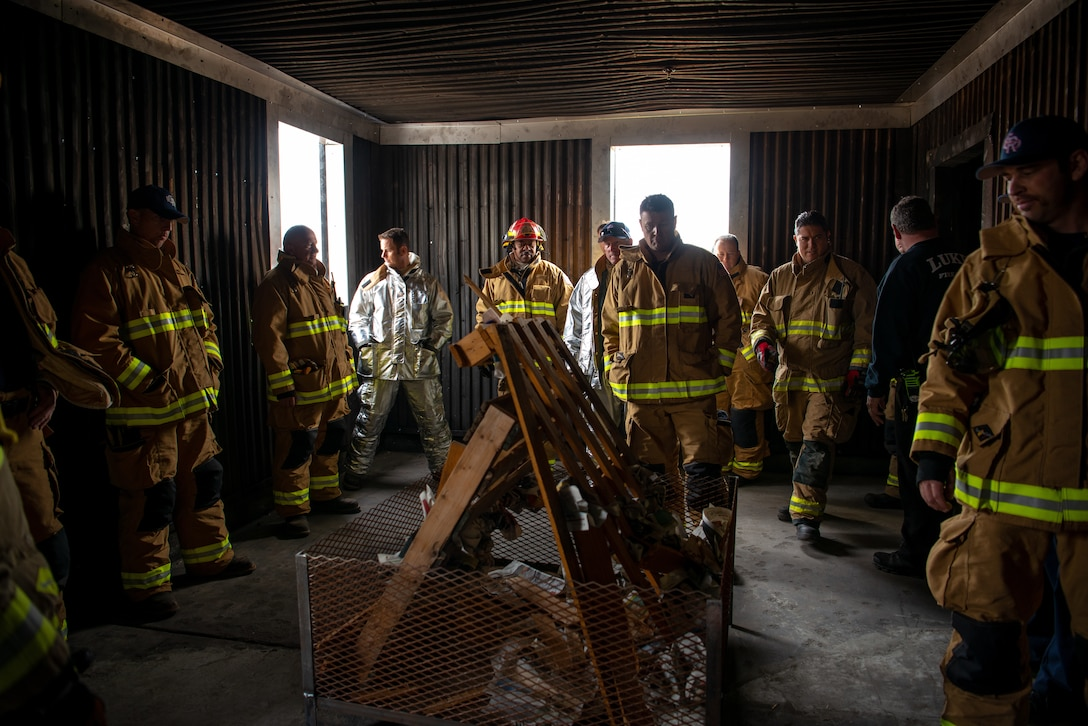 Luke firefighters assigned to the 56th Civil Engineer Squadron Fire Department and Gila Bend Air Force Auxiliary Field, listen to a safety brief before igniting a training structural fire, Nov. 14, 2018 at Luke Air Force Base, Ariz.