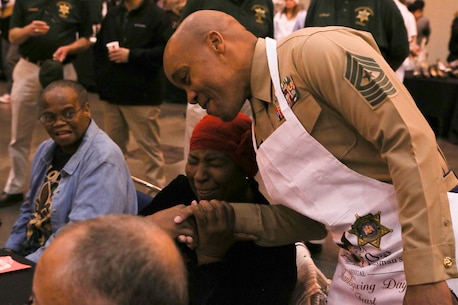 Sgt. Maj. Cortez Brown, 6th Marine Corps District sergeant major, interacts with a community member while serving Thanksgiving meals at the Ernest N. Morial Convention Center in New Orleans, Louisiana, November 22, 2018. Items on the menu included family, thanks and plenty of smiles.