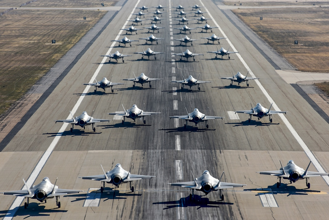About 36 F-35A aircraft taxi in formation on a flightline.