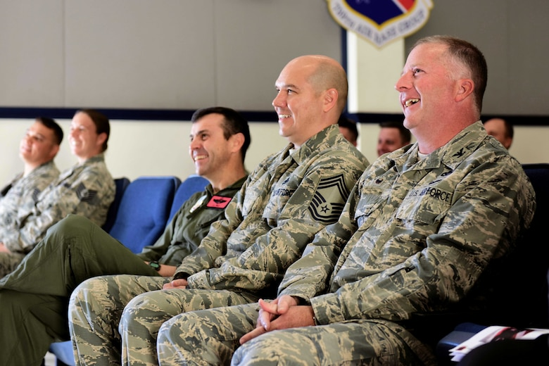 Creech Air Force Base leadership laugh as Kiara, 799th Security Forces Squadron Military Working Dog, performs her last bite during her retirement ceremony at Creech Air Force Base, Nevada, Nov. 15, 2018. Kiara began her MWD career in 2009. Three assignments, nine years and 10 handlers later, she is retiring from her time as a U.S. Air Force MWD. (U.S. Air Force photo by Airman 1st Class Haley Stevens)