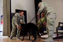 Kiara, 799th Security Forces Squadron Military Working Dog, receives a bone from Tech. Sgt. Christine, 799th SFS kennel master, on behalf of Kiara's MWD unit during her retirement ceremony at Creech Air Force Base, Nevada, Nov. 15, 2018. Due to the strict MWD diet, the dogs do not receive treats such as the bone she was presented with upon her separation from the service. (U.S. Air Force photo by Airman 1st Class Haley Stevens)