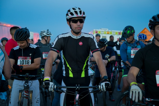 """A competitor within the bike route participates in the first annual Telegraph Pass Challenge in Yuma, Ariz., Nov. 3, 2018. The challenge, coordinated by Marine Corps Community Services (MCCS), offered participants the opportunity to compete for first, second, or third place in either a 5 mile run, 5 mile bike route, or both. The course included a """"Blue Mile"""" which is typically the most difficult portion of the racing event being a silent mile. The """"Blue Mile"""" honors and remembers all fallen heroes of the Military, Police, and Fire Department. (U.S. Marine Corps photo by Lance Cpl. Joel Soriano)"""