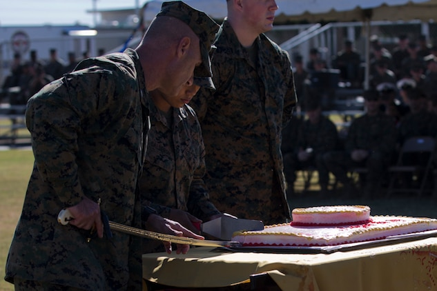 U.S. Marine Corps Col. David A. Suggs, commanding officer, Marine Corps Air Station Yuma, cuts a piece of birthday cake in the 243rd Marine Corps birthday uniform pageant at the Parade Deck on Marine Corps Air Station Yuma, Ariz., Nov. 8, 2018. The annual ceremony was held in honor of the 243rd Marine Corps birthday, showcasing historical uniforms to honor Marines of the past, present and future while signifying the passing of traditions from one generation to the next. (U.S. Marine Corps photo by Lance Cpl. Joel Soriano)