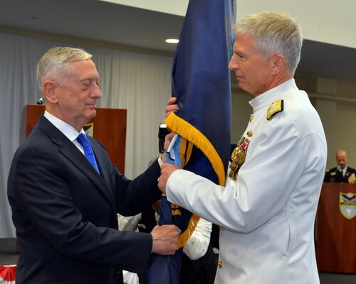 U.S. Secretary of Defense James Mattis, left, passes the U.S. Southern Command guidon to Adm. Craig S. Faller, USN, incoming commander of SOUTHCOM.