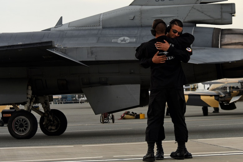U.S. Air Force Tech. Sgt. Dominic Dizes, F-16 Viper Demonstration Team (VDT) dedicated crew chief, front, and Tech. Sgt. Stephen Mullins, F-16 VDT avionics specialist, hug after launching out their pilot on the flight line at Sakhir Airbase, Kingdom of Bahrain, Nov. 16, 2018.
