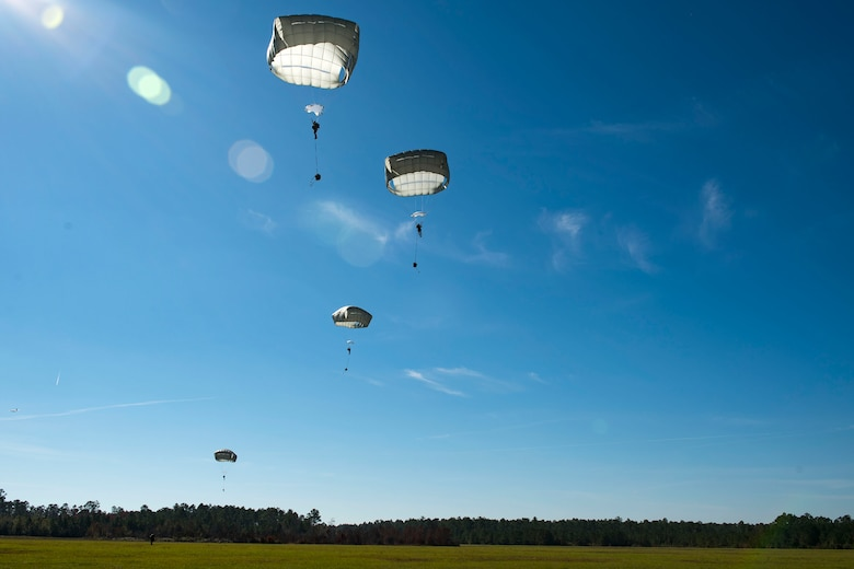 Airmen from the 93d Air Ground Operations Wing parachute down during static-line jump training, Nov. 21, 2018, at Moody Air Force Base, Ga. The overall objective of the training was to increase jumpers' skills, knowledge and proficiency in regards to airborne operations. During a static-line jump, the jumper is attached to the aircraft via the 'static-line', which automatically deploys the jumpers' parachute after they've exited the aircraft. (U.S. Air Force photo by Airman 1st Class Erick Requadt)