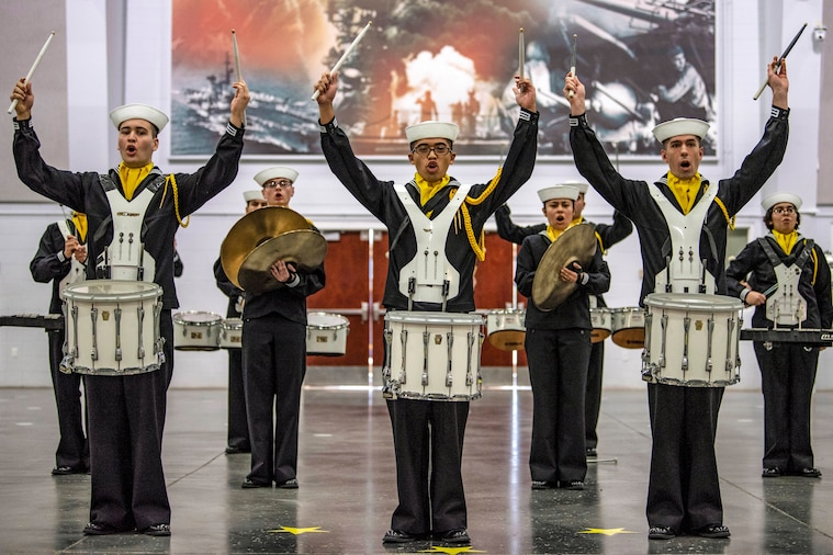 Recruits with drums hold up drumsticks during a performance.