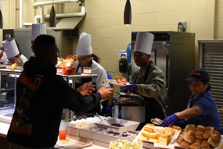 U.S. Air Force Maj. Michael Quinn, 17th Contracting Squadron commander, hands out food during the Thanksgiving Day lunch at the Western Winds Dining Facility on Goodfellow Air Force Base, Texas, Nov. 22, 2018. For those stationed at Goodfellow that were unable to go home to family and friends the lunch was a way to spread a bit of holiday spirits. (U.S. Air Force photo by Airman 1st Class Zachary Chapman/Released)