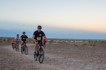 """U.S. Marine Corps Sgt. Maj. David M. Leikwold, sergeant major of Marine Corps Air Station Yuma leads a line of bike competitors participating in the first annual Telegraph Pass Challenge in Yuma, Ariz., Nov. 3, 2018. The challenge, coordinated by Marine Corps Community Services (MCCS), offered participants the opportunity to compete for first, second, or third place in either a 5 mile run, 5 mile bike route, or both. The course included a """"Blue Mile"""" which is typically the most difficult portion of the racing event being a silent mile. The """"Blue Mile"""" honors and remembers all fallen heroes of the Military, Police, and Fire Department. (U.S. Marine Corps photo by Sgt. Allison Lotz)"""