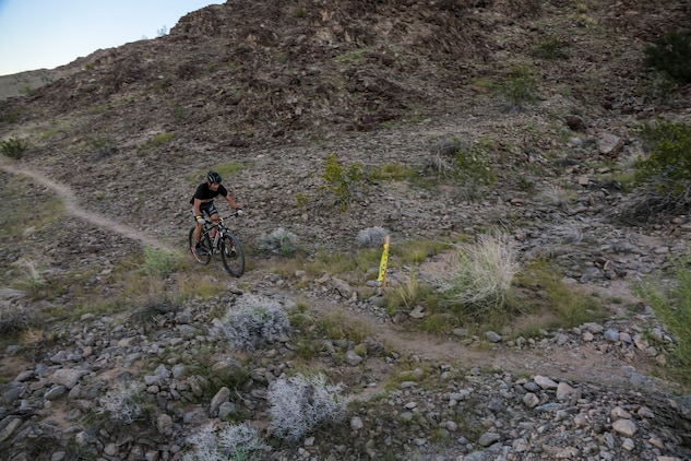 """A competitor within the bike route participates in the first annual Telegraph Pass Challenge in Yuma, Ariz., Nov. 3, 2018. The challenge, coordinated by Marine Corps Community Services (MCCS), offered participants the opportunity to compete for first, second, or third place in either a 5 mile run, 5 mile bike route, or both. The course included a """"Blue Mile"""" which is typically the most difficult portion of the racing event being a silent mile. The """"Blue Mile"""" honors and remembers all fallen heroes of the Military, Police, and Fire Department. (U.S. Marine Corps photo by Sgt. Allison Lotz)"""