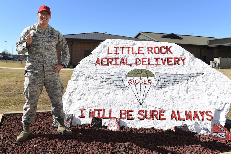 A man wearing a red hat and a U.S. Air Force Airman Battle Uniform stands to the left of a white rock that says 'Little Rock Aerial Delivery, I will be sure always.' The man holds a white plastic piece shaped like a 'U' in his right hand.