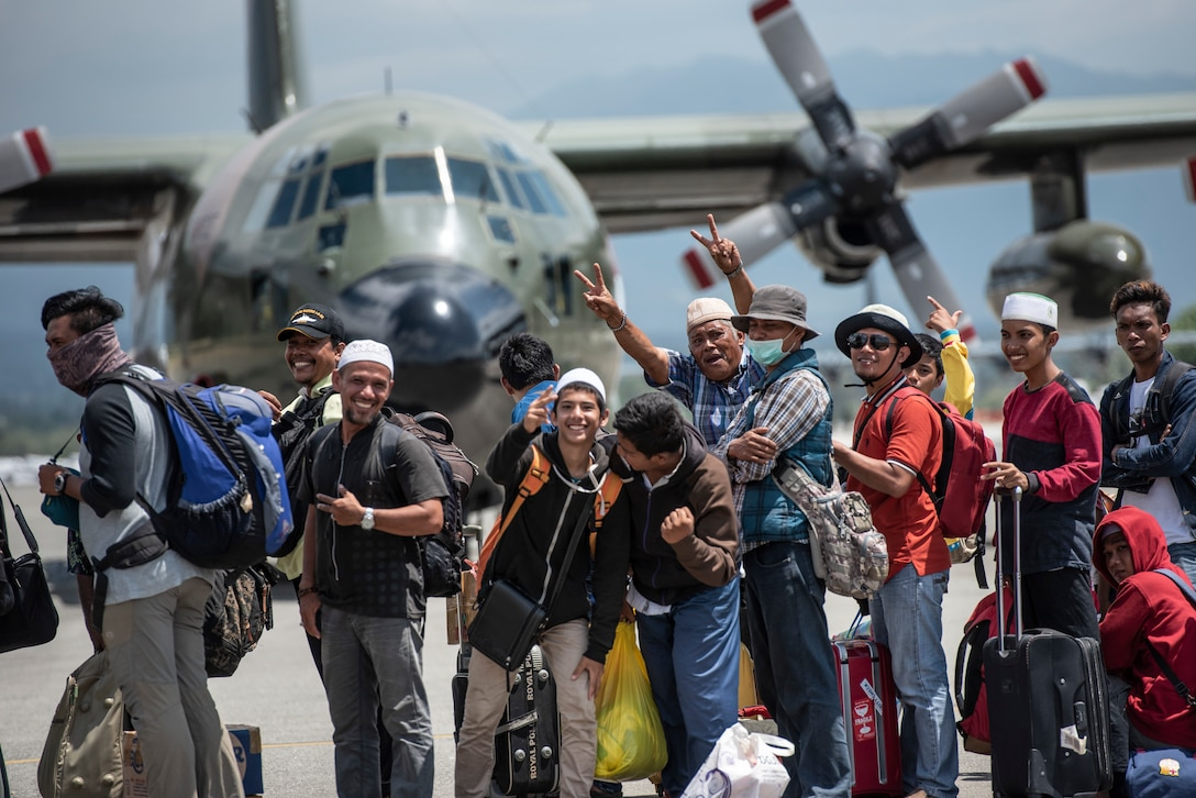 """A group of displaced people from Indonesia hold-up a peace sign and say """"Thank you America"""" prior to boarding a U.S. Air Force C-130J Super Hercules in Palu, Indonesia Oct. 10, 2018."""