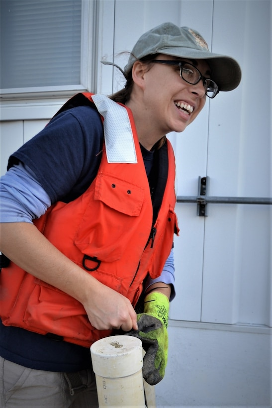 Woman in orange life vest and glasses smiles off camera to the right while working outside on a plastic tube used for oyster reef restoration