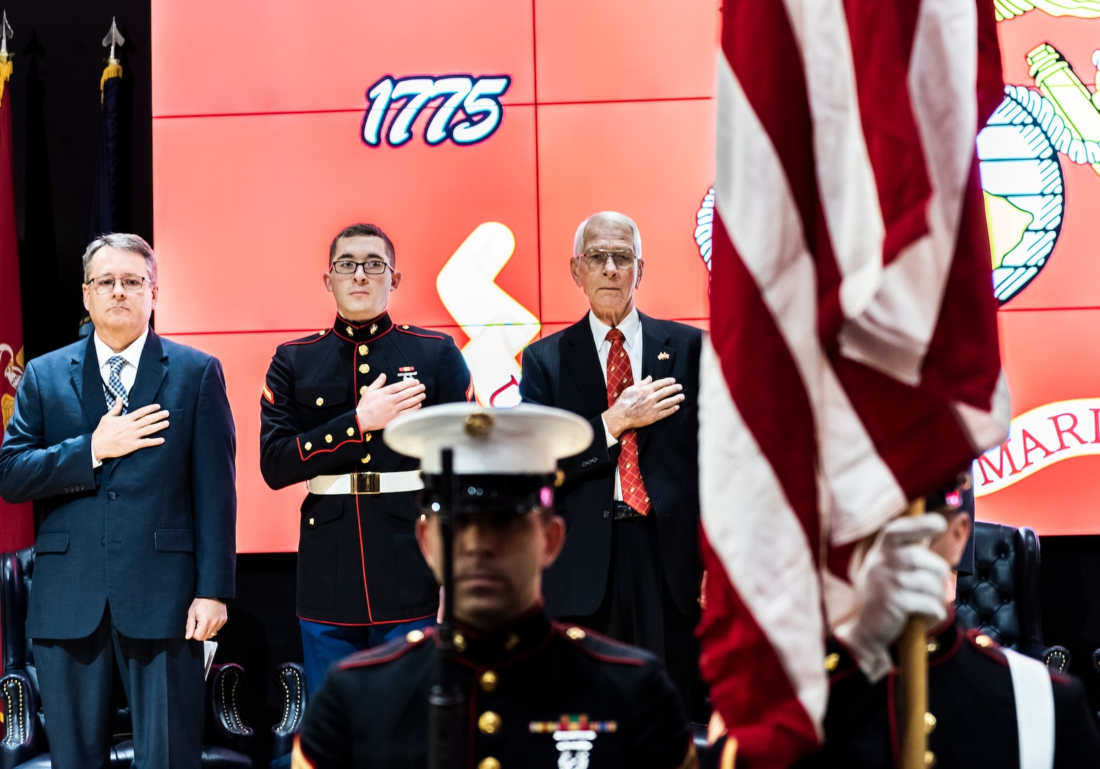 Three men on stage have right hand over heart as Marines present the colors during birthday celebration