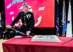 A Marine on a stage prepares to cut a birthday cake on a table