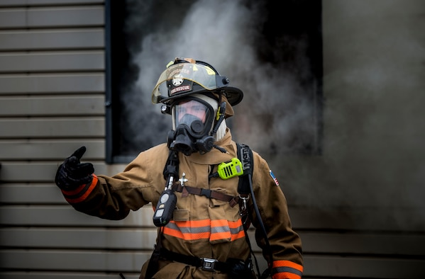 U.S. Air Force Airman 1st Class Austin Perry, 20th Civil Engineer Squadron, firefighter signals a fellow firefighter at Shaw Air Force Base, S.C., Nov. 20, 2018.