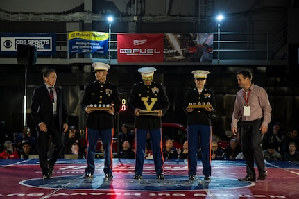 Fresno State University Wrestling Head Coach Troy Steiner (left) and Stanford University Wrestling Head Coach Jason Borrelli (right) exchange challenge coins at the beginning of the Battle on the Midway aboard the USS Midway, San Diego, Calif., Nov. 20, 2018. (U.S. Marine Corps photo by Sgt. Christian Cachola)