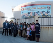 """Mayor Julie Hackbarth-McIntyre and San Bernardino County Supervisor James Ramos pose with family members of the Barstow area Marines who served as Navajo Code Talkers, during an event dedicating the new Navajo Cold Talker Mural to them held in Barstow, Calif., Nov. 11. The families of the five United States Marines who served as Navajo Code Talkers during World War II, were able to speak to the crowd about their relatives' proud service to the Corps and to the United States of America. The ceremony included awards, certificates, and high praise from Mayor Julie Hackbarth-McIntyre, San Bernardino County Supervisor James Ramos, Assemblyman Jay Obernolte, as well as the commanding officer of Marine Corps Logistics Base Barstow. After their service during the war, the Marines came to the Barstow area, working for MCLB Barstow until their service ended. Some returned to work as civilians until they retired. The Marines honored on the mural, left to right: Jimmy L. Benally,  4th Marine Division, was awarded the Silver Medal; John Chee, 2nd Marine Division, was awarded the Gold Medal; Nelson Draper, Sr., 2nd Marine Division, was awarded the Silver Medal; Joe Morris, Sr., 6th Marine Division, was awarded the Silver Medal; Joseph H. Towne, 3rd Marine Division, was awarded the Silver Medal. Each entered into the Marine Corps as radiomen, unaware that their primary mission would be to use the secretive Navajo language as a code to help transmit top secret, mission-critical message to support the Marine Corps' war efforts. Their motto, """"Our Weapon Was Our Language"""" is proudly displayed on the mural honoring these hometown heroes."""