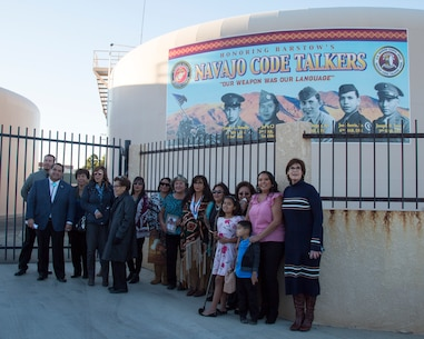 "Mayor Julie Hackbarth-McIntyre and San Bernardino County Supervisor James Ramos pose with family members of the Barstow area Marines who served as Navajo Code Talkers, during an event dedicating the new Navajo Cold Talker Mural to them held in Barstow, Calif., Nov. 11. The families of the five United States Marines who served as Navajo Code Talkers during World War II, were able to speak to the crowd about their relatives' proud service to the Corps and to the United States of America. The ceremony included awards, certificates, and high praise from Mayor Julie Hackbarth-McIntyre, San Bernardino County Supervisor James Ramos, Assemblyman Jay Obernolte, as well as the commanding officer of Marine Corps Logistics Base Barstow. After their service during the war, the Marines came to the Barstow area, working for MCLB Barstow until their service ended. Some returned to work as civilians until they retired. The Marines honored on the mural, left to right: Jimmy L. Benally,  4th Marine Division, was awarded the Silver Medal; John Chee, 2nd Marine Division, was awarded the Gold Medal; Nelson Draper, Sr., 2nd Marine Division, was awarded the Silver Medal; Joe Morris, Sr., 6th Marine Division, was awarded the Silver Medal; Joseph H. Towne, 3rd Marine Division, was awarded the Silver Medal. Each entered into the Marine Corps as radiomen, unaware that their primary mission would be to use the secretive Navajo language as a code to help transmit top secret, mission-critical message to support the Marine Corps' war efforts. Their motto, ""Our Weapon Was Our Language"" is proudly displayed on the mural honoring these hometown heroes."