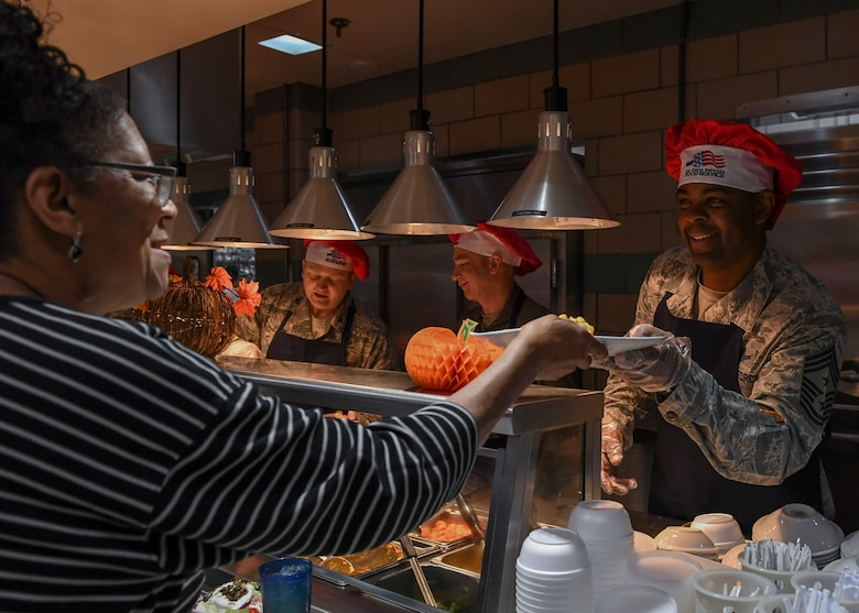 U.S. Air Force Chief Master Sgt. Jay Harris, 1st Fighter Wing command chief, hands a Thanksgiving meal to a Crossbow Dining Facility patron at Joint Base Langley-Eustis, Virginia, Nov. 22, 2018.