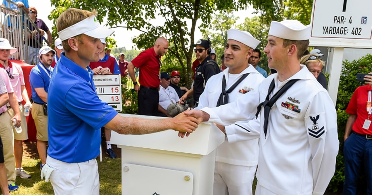 Golfer Billy Hurley III shakes hands with sailors on golf course.