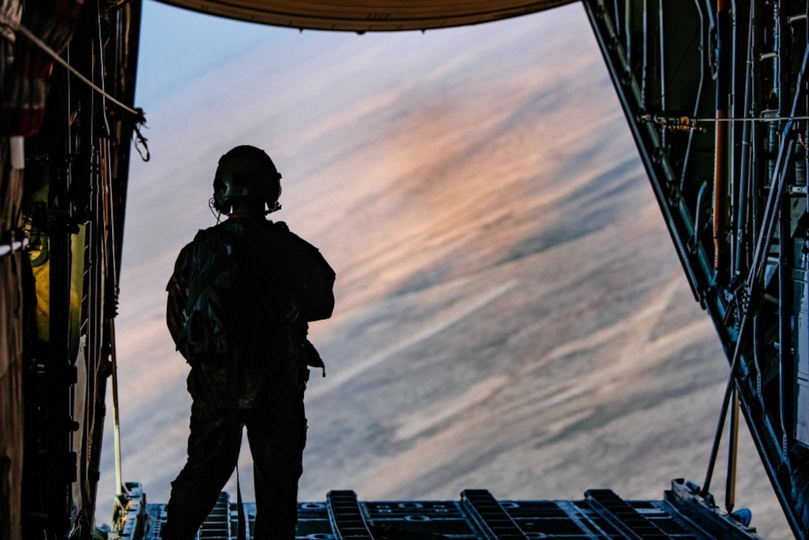An loadmaster observes a jettisoned load of supplies from the rear of an aircraft in flight.