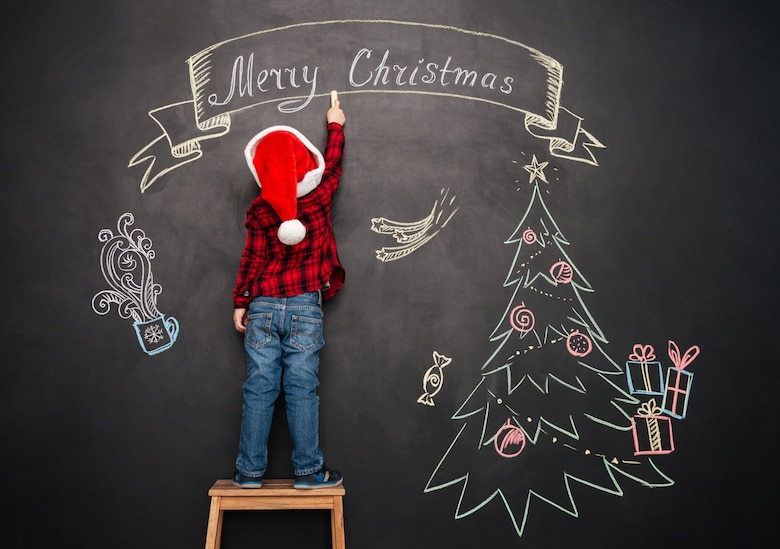 Image of little child wearing hat standing on stool near Christmas tree while drawing on blackboard.