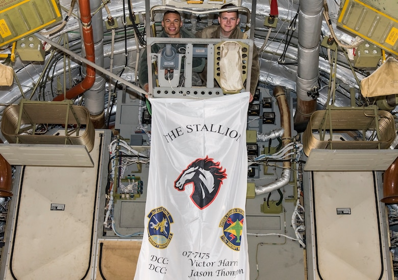 Senior Airman Victor Harris, right, Dedicated Crew Chief, and Airman 1st Class Jason Thompson, left, Assistant DCC, both assigned to the 736th Aircraft Maintenance Squadron, hold their aircraft flag where it will hang Nov. 21, 2018, at Dover Air Force Base, Del. Each of the 13 C-17 Globemaster III aircraft assigned to Dover will display a flag showing the unofficial name of the aircraft, tail number, and the names of the DCC and ADCC. (U.S. Air Force photo by Roland Balik)
