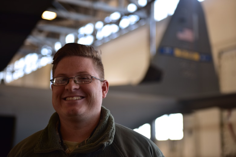 A man wearing the Airman Battle Uniform stands in front of a C-130J.