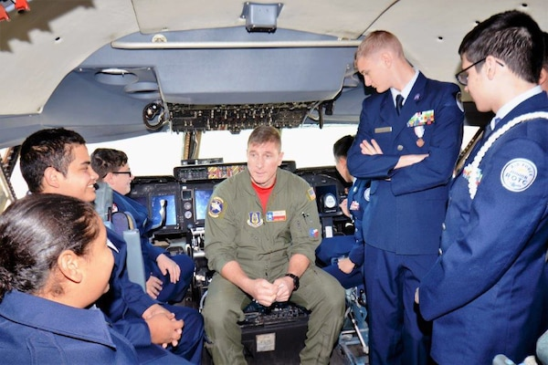 Flight Engineer Tech. Sgt. Ryan Lohrer with the 68th Airlift Squadron, Joint Base San Antonio-Lackland, seated center in the new upgraded C-5M Super Galaxy, Nov. 16, 2018, explains the different controls located in the cockpit to Porter High School Air Force Junior Reserve Officers' Training Corps cadets.