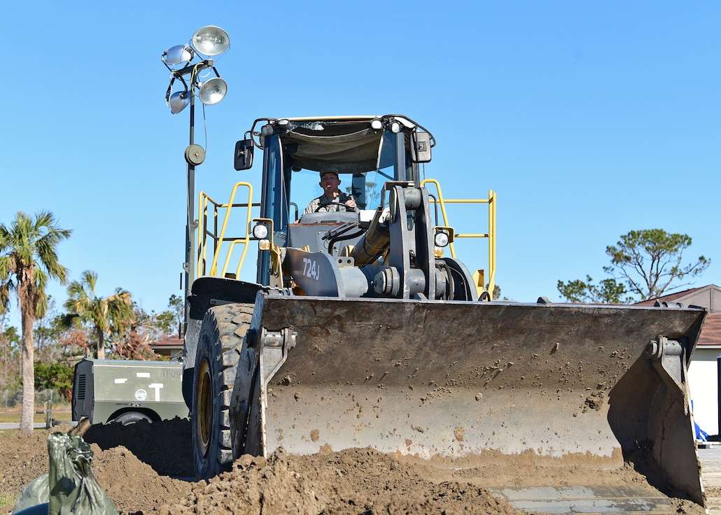 Senior Airman Justin Courtney, a member of Task Force Phoenix and the 375th Civil Engineer Squadron pavements and heavy equipment operator, transfers soil while at Tyndall Air Force Base, Fla., Nov. 27, 2018. Task Force Phoenix is responsible for large-scale clean up and reconstruction after Hurricane Michael ravaged Tyndall Air Force Base and the panhandle of Florida. (U.S. Air Force photo by Senior Airman Isaiah J. Soliz)